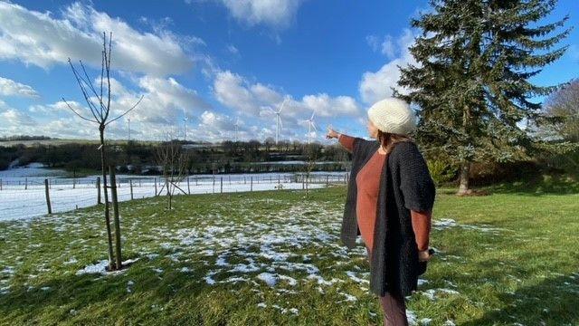 Derrière la maisond'Aurélie, une habitante Echauffour dans l'Orne, avec les éoliennes en arrière-plan. (MARC BERTRAND / RADIOFRANCE)