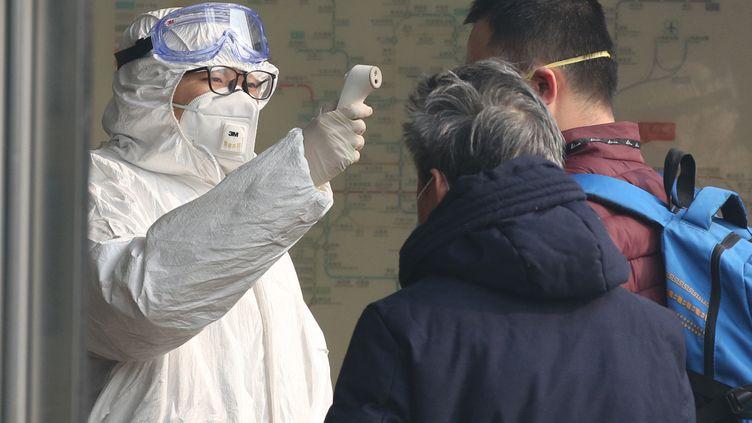 Un officier sanitaire prend la température de deux passagers à l'entrée d'une station de métro de Pékin, le 28 janvier 2020. (KOKI KATAOKA / YOMIURI / AFP)