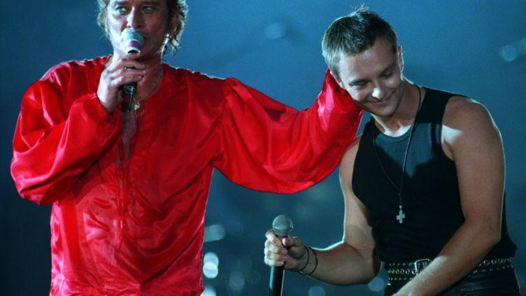 Cette fois-ci en rouge, Johnny Hallydaymonte sur scène accompagné de son fils, David, au Parc des princes (Paris), le 18 juin 1993. (MAXPPP)