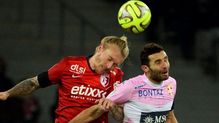 Simon Kjaer (Lille) à la lutte avec Cédric Barbosa (Evian-TG) (DENIS CHARLET / AFP)