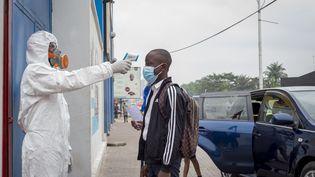 Un élève fait mesurer sa température avant d'entrer à l'école, lors de la reprise des cours après le confinement du Covid-19 à Kinshasa, le 10 août 2020. (ARSENE MPIANA / AFP)
