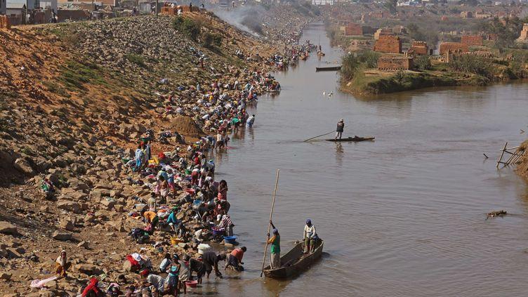 Des centaines de personnes nettoient leurs vêtements dansla rivière Ikopa près d'Antananarivo, la capitale de Madagascar, le 25 octobre 2013. (SCHALK VAN ZUYDAM / AP / SIPA)