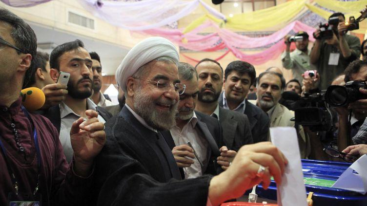 Le candidat à la présidentielle en Iran,Hassan Rohani,glisse son bulletin dans l'urne, le 14 juin 2013 à Téhéran (Iran). (REUTERS)