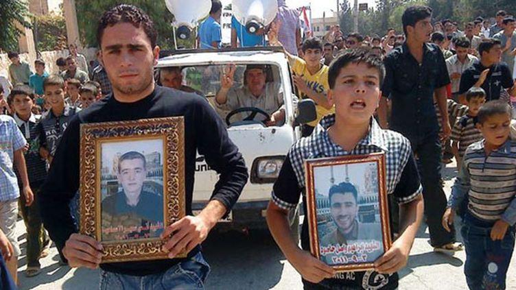 Des manifestants opposés au régime du président syrien Bachar Al-Assad défilent avec les portraits de personnes mortes dans les violences, à Maaret Harma, dans la province d'Idlib (Syrie), le 9 septembre 2011. La photo a été prise par un journaliste, avec son téléphone portable. (AP / SIPA)