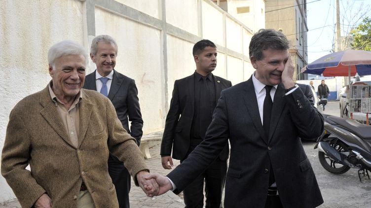 Guy Bedos tient la main d'Arnaud Montebourg, le 11 décembre 2016, à Alger (Algérie). (RYAD KRAMDI / AFP)