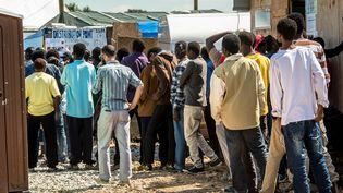 """Des migrants dans la """"jungle"""" à Calais font la queue pour une distribution de nourriture, le 24 juillet 2016. (PHILIPPE HUGUEN / AFP)"""