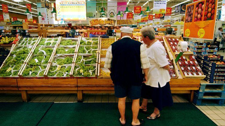 Un couple de retraités fait son choix devant un étal de fruits et légumes dans une grande surface du Calvados, en août 2004. (MYCHELE DANIAU / AFP)