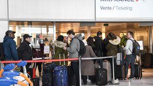 Des voyageurs attendent devant le guichet de la compagnie Air France, le 12 mars 2020. (BERTRAND GUAY / AFP)