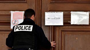 Un policier ferme les portes de la salle d'audience où se déroule le procès de Joël Le Scouarnec, le 13 mars 2020 à Saintes (Charente-Maritime). (GEORGES GOBET / AFP)