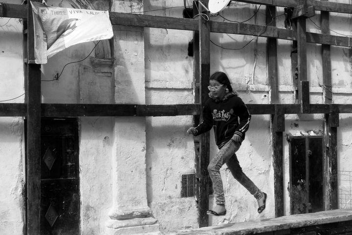 """Dans la Casbah d'Alger, cette petite fille court sur un parapet devant le drapeau algérien sur lequel est écrit """"One, Two, Three, viva l'Algérie !"""" (Lotfi Mokdad)"""