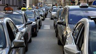 Des chauffeurs de taxi bloquent le trafic à Lyon (Rhône), pour protester contre la concurrence des voitures de tourisme avec chauffeur, le 12 février 2014. (JEAN-PHILIPPE KSIAZEK / AFP)