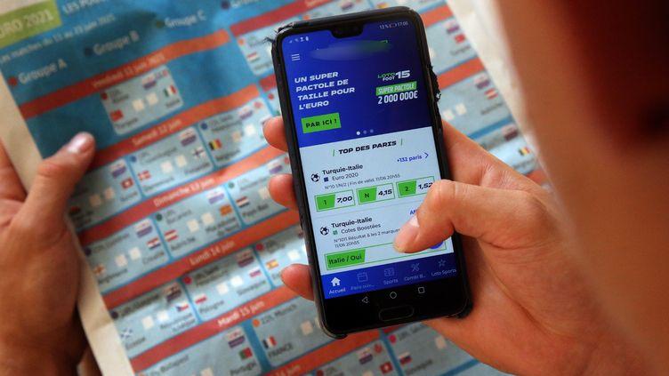 Un joueur fait un pari sportif en ligne sur son smartphone sur les matchs de football de l'Euro. Photo d'illustration. (VANESSA MEYER / MAXPPP)