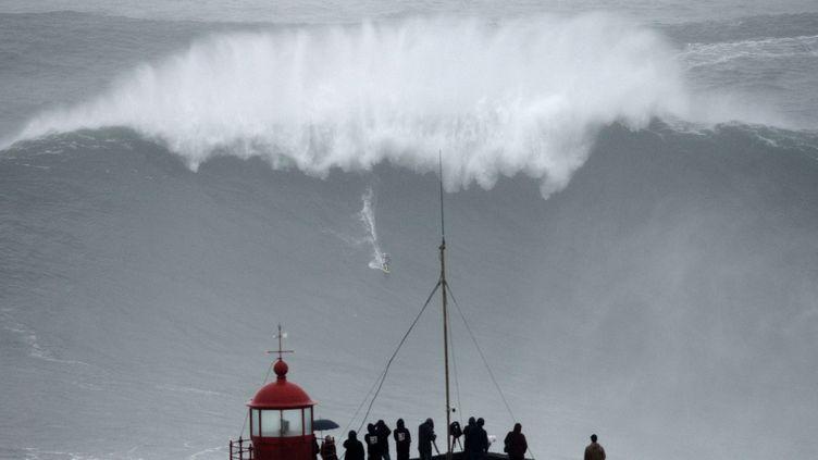 Le brésilien Carlos Burle surfe une vague géante, le 28 octobre 2013 à Nazaré (Portugal). (FRANCISCO LEONG / AFP)