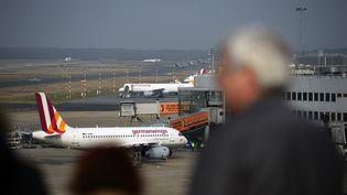 Un homme regadre un avion de Germanwings sur l'aéroport de Düsseldorf le 24 mars 2015. (SASCHA SCHUERMANN / AFP)