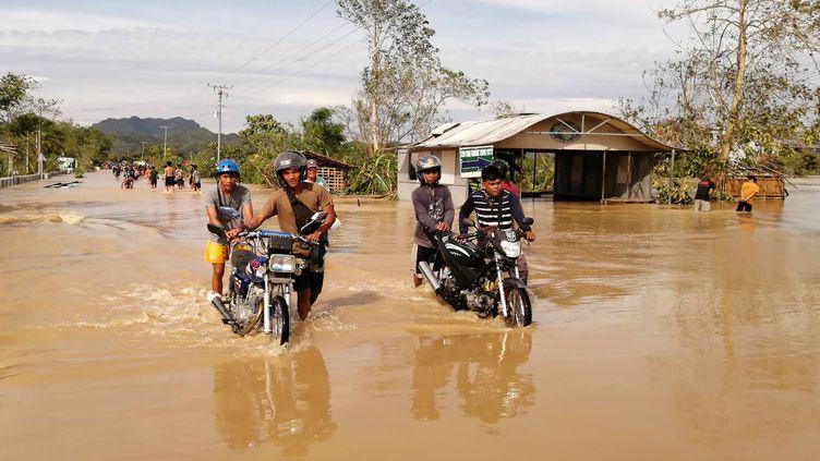 Des habitants affrontent les eaux après de fortes précipitations dues au passage du typhon Phantone, mercredi 25 décembre 2019 à Ormoc (Philippines). (RONALD FRANK DEJON / AFP)