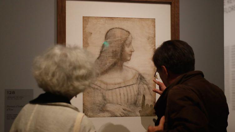 """Deux visiteurs admirent le """"Portrait d'Isabelle d'Este"""" à l'ouverture de l'exposition Léonard de Vinci au musée du Louvre, le 22 octobre 2019. (FRANCOIS GUILLOT / AFP)"""