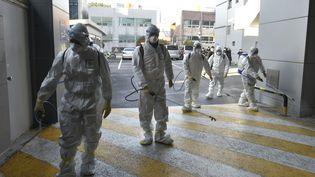 Des personnels des services de santé devant la branche locale del'Eglise de Shincheonji, ou Temple du Tabernacle du témoignage à Daegu (Corée du Sud), le 19 février 2020. (HANDOUT / DAEGU METROPOLITAN CITY NAMGU / AFP)