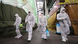 Lors d'une opération de désinfection d'un marché de la ville sud-coréenne de Daegu, principal foyer du Covid-19, en Corée du Sud, le 23 février 2020. (YONHAP / AFP)
