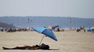 Une femme bronze sur la plage de Deauville (Calvados), le 1er juillet 2015. (CHARLY TRIBALLEAU / AFP)