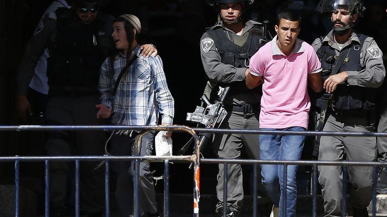 Les forces de sécurité israéliennes arrêtent un Palestinien, après des heurts sur l'Esplanade des mosquées, à Jérusalem, le 26 juillet 2015. (AHMAD GHARABLI / AFP)
