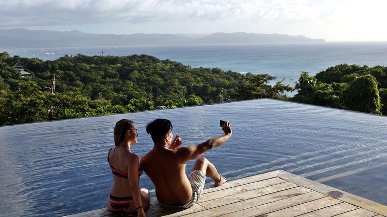 Deux jeunes gens se prennent en photo au bord d'une piscine, aux Philippines, le 7 décembre 2018. (ALEJANDRO ERNESTO / DPA / AFP)