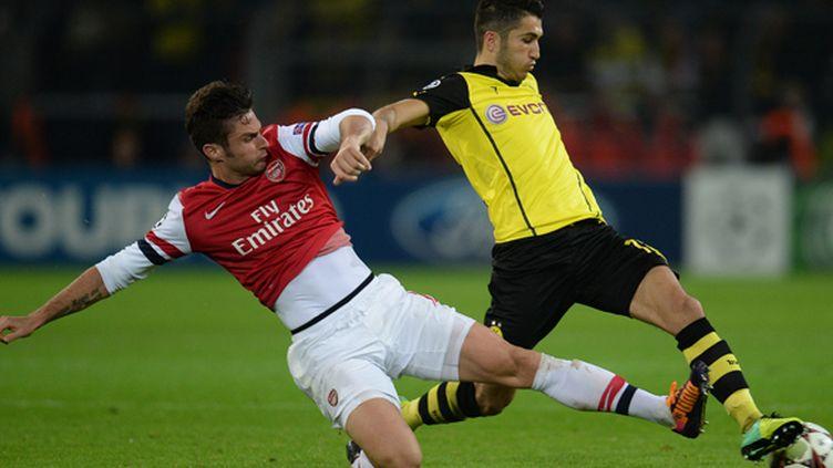 Le Gunner Mikel Arteta tacle le milieu de terrain du Borussia Dortmund Nuri Sahin lors de la Ligue des champions 2013/2014 (PATRIK STOLLARZ / AFP)