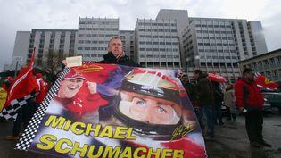 Un fan de Michael Schumacher le 3 janvier 2017, devant l'hôpital de Grenoble où le pilote de F1 a été hospitalisé après son accident, en décembre 2013. (ALEX GRIMM / BONGARTS / GETTYIMAGES)
