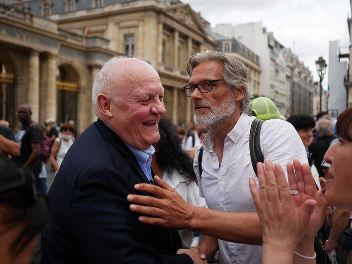 Le candidat déclaré à l'élection présidentielle François Asselineau (à g.) salue des manifestants contre le pass sanitaireet la vaccination contre le Covid-19, à Paris, le 24 juillet 2021. (DJOUDI HAMANI / HANS LUCAS / AFP)
