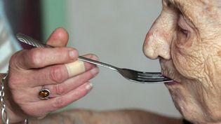 Une personne donne à manger à une dame agée. (ROMAIN PERROCHEAU / AFP)