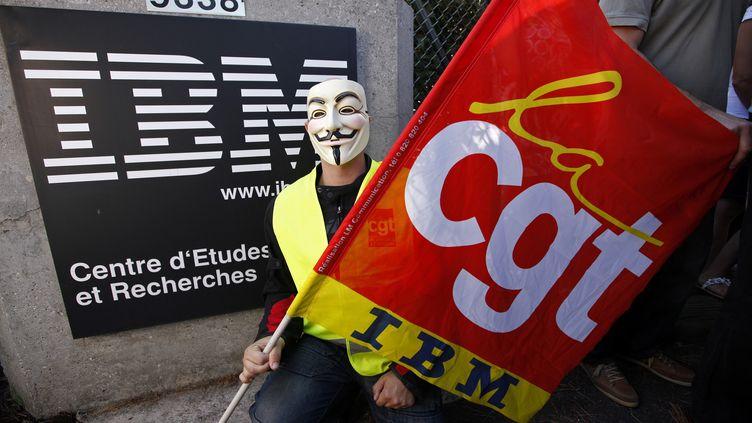 Un salarié d'IBM, masqué, porte un drapeau de la CGT, au centre de recherches IBM de La Gaude (Alpes-Maritimes), le 9 août 2012. (ERIC GAILLARD / REUTERS)
