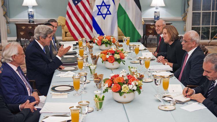 La ministre de la Justice israélienne, Tzipi Livni, et le négociateur palestinien Saeb Erakat (D), attablés face au secrétaire d'Etat américain, John Kerry, le 29 juillet 2013 à Washington. (PAUL J. RICHARDS / AFP)