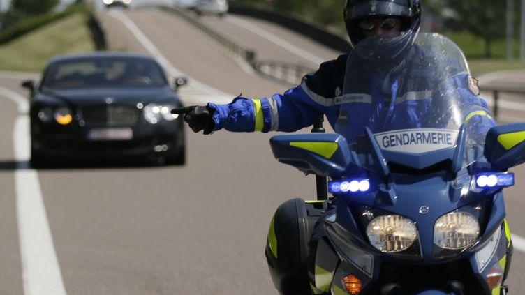 Un gendarme arrête une voiture sur l'autoroute à Beaune (Côte-d'Or), le 6 juillet 2013. (KENZO TRIBOUILLARD / AFP)