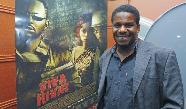Le cinéaste Djo Tunda Wa Munga, devant l'affiche de son film, lors de sa projection à l'AFI Silver Theatre and Cultural Center le 7 juin 2011 à Silver Spring (Maryland, Etats-Unis). (Leigh Vogel / GETTY IMAGES NORTH AMERICA / AFP)