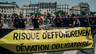Des militants du collectifExtinction Rébellion tentent de bloquer le pont de Sully, à Paris, le 28 juin 2019. (MATHIAS ZWICK / HANS LUCAS / AFP)