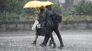 Deux passants sous la pluie à Sydney, le 17 janvier 2020. (STRINGER / X80002 / AFP)