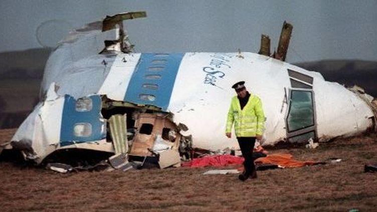 Policier devant les restes du cockpit du boeing 747 de la Pan Am qui s'est écrasé à Lockerbie (Ecosse), le 22 décembre 1988. L'attentat avait fait 270 morts, dont onze habitants de la cité écossaise. (ROY LETKEY / AFP)