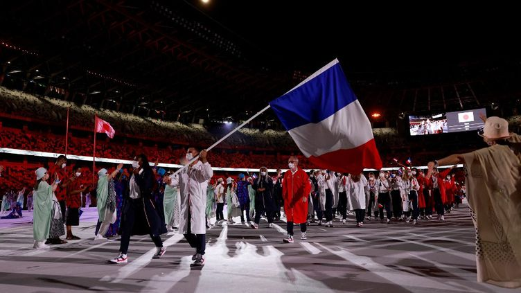 Les deux porte-drapeaux français, lajudokaClarisse Agbegnenou et le gymnaste Samir Aït Saïd, ont amené les 80 athlètes tricolores autorisés à participer à la cérémonie sur les 378 qualifiés. En tout,seulement 6 000 athlètes ont représenté leur pays durant plus de trois heures decérémonie, célébrant la culture japonaise et l'esprit olympique. (ODD ANDERSEN / AFP)