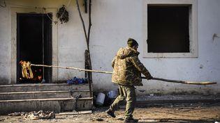 Un habitant du village deCharektar, dans la région du Haut-Karabakh, brûle sa maison, le 14 novembre 2020. (ALEXANDER NEMENOV / AFP)