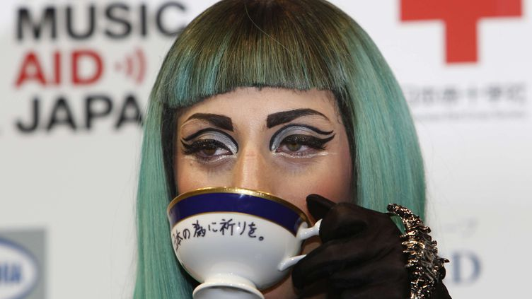 Lady Gaga pose avec sa tasse de thé lors d'une conférence de presse le 23 juin 2011 à Tokyo (Japon). La tasse a été mise aux enchères le 30 avril 2012. (SHIZUO KAMBAYASHI / AP / SIPA)