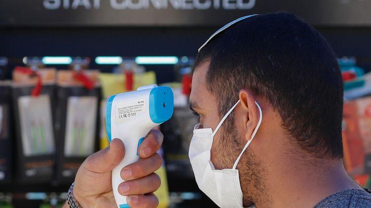 Un employé d'un magasin d'électronique prend la température d'un client pendant la pandémie de Covdi-19 à Jérusalem, le 20 avril 2020. (EMMANUEL DUNAND / AFP)