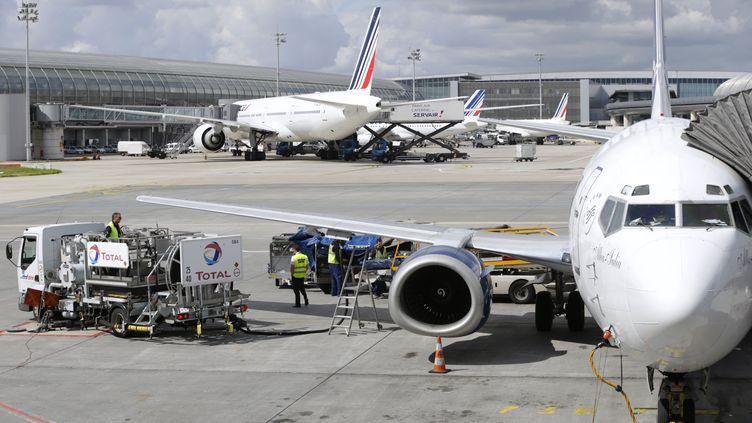 Des agents au sol préparent un avion de la compagnie Air France, le 18 août 2014, à l'aéroport de Roissy-Charles-de-Gaulle. (KENZO TRIBOUILLARD / AFP)