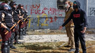 Des manifestants face à des policiers de l'Etat du Minnesota, à Minneapolis, le 29 mai 2020. (KEREM YUCEL / AFP)