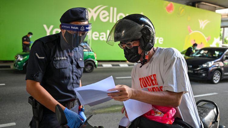 En Malaisie, retour du confinement et des autorisations de déplacement en raison d'une résurgence de Covid-19. Kuala Lumpur le 1er juin 2021 (MOHD RASFAN / AFP)