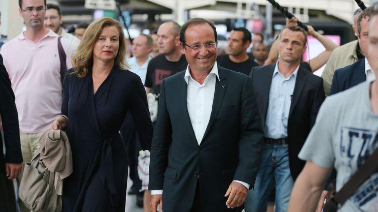 Le président François Hollande et sa compagne, Valérie Trierweiler, à son arrivée à la gare de Lyon, à Paris, le 19 août. (THOMAS SAMSON / AFP)