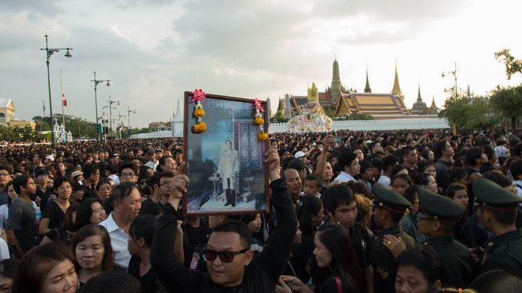 Les Thaïlandais à genoux dans les ruesde Bangkok au passage du convoi funéraire de leur roi Bhumibol Adulyadej, le 14 octobre 2016 (ROBERTO SCHMIDT / AFP)