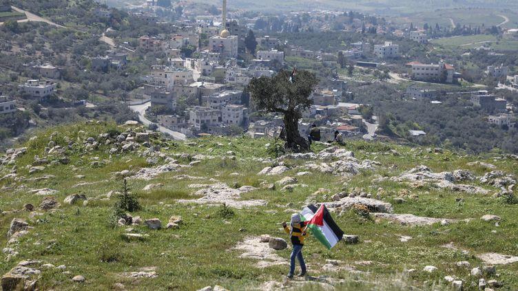 Un personne porte le drapeau de la Palestine près de Naplouse en Cisjordanie, le 29 mars 2021. (JAAFAR ASHTIYEH / AFP)