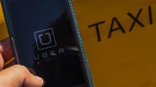 Un utilisateur ouvre l'application du service de VTC Uber, à Barcelone, le 1er juillet 2014. (DAVID RAMOS / GETTY IMAGES / AFP)