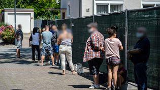 Des habitants patientent avant un dépistage du Covid-19, mardi 23 juin 2020 àGütersloh (Allemagne). (GUIDO KIRCHNER / DPA / AFP)
