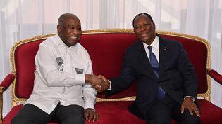 Le président ivoirien Alassane Ouattara (à droite) serre la main de son prédécesseur et ancien rival Laurent Gbagbo (à gauche), au palais présidentiel à Abidjan, le 27 juillet 2021. (ISSOUF SANOGO / AFP)