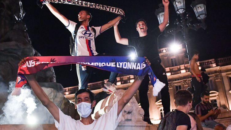 Les supporters lyonnais fêtent, à Lyon, la qualification de l'OL en quart de finale de la Ligue des Champions, le 7 août.   (PHILIPPE DESMAZES / AFP)
